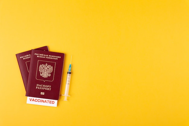 Passports with vaccinated stamp on blank syringe with vaccine on yellow surface