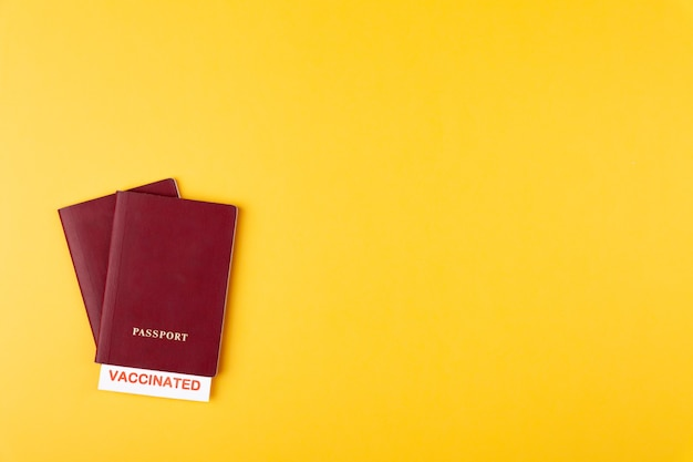 Passports with vaccinated stamp on yellow background