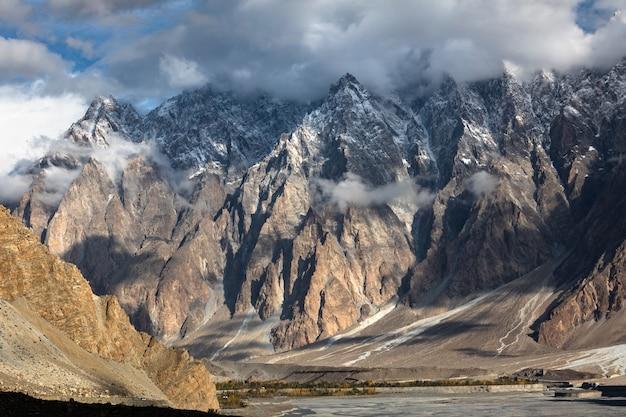 Конусы пассу горный хребет каракорум долина реки хунза, пакистан. пасмурный день пейзаж