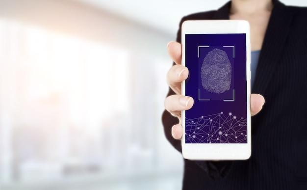 指紋によるパスワード制御。明るいぼやけた背景にデジタルホログラム指紋サイン付きの白いスマートフォンを手に持ってください。生体認証とセキュリティの概念。