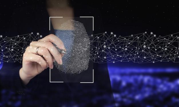 지문을 통한 암호 제어. 디지털 그래픽 펜을 들고 도시의 어두운 배경에 디지털 홀로그램 지문 기호를 그립니다. 사이버 보안 및 데이터 보호.