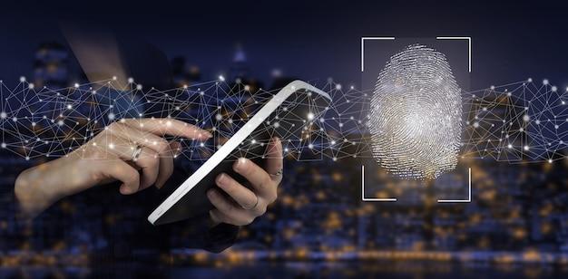 指紋によるパスワード制御。街の暗いぼやけた背景にデジタルホログラム指紋サイン付きの手タッチ白いタブレット。生体認証とセキュリティの概念。