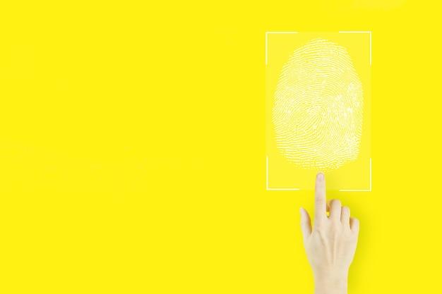 지문을 통한 암호 제어. 노란색 배경에 홀로그램 지문 스캔으로 가리키는 젊은 여성의 손 손가락. 몰입형 기술의 미래와 사이버네틱.