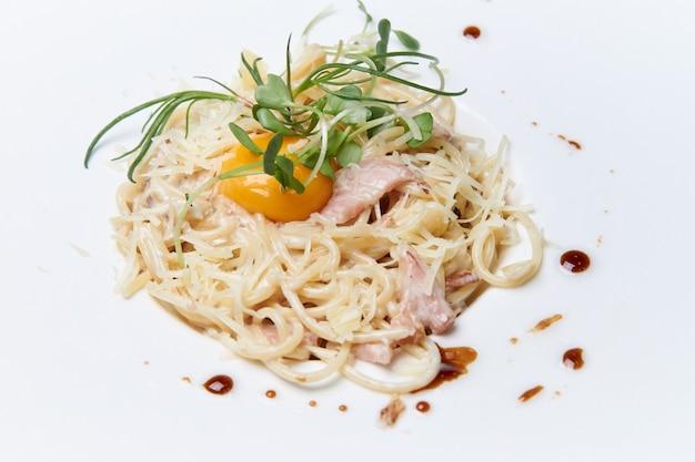 Pasta alla carbonara on a white dish.