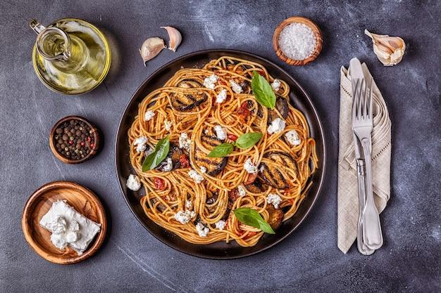 Паста алла норма. традиционная итальянская кухня с баклажанами, помидорами, сыром и базиликом, вид сверху.