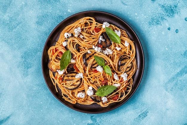 Pasta alla norma - традиционные итальянские блюда с баклажанами, помидорами, сыром и базиликом, вид сверху.