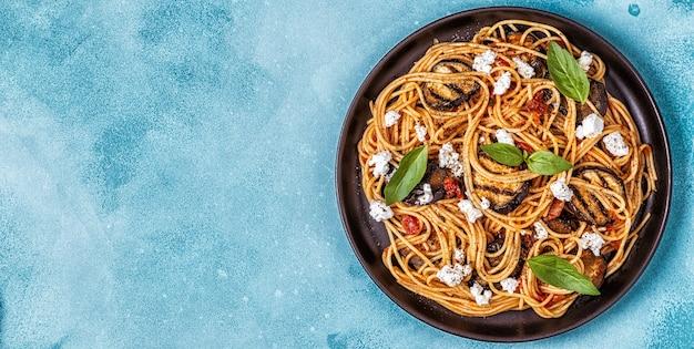 Паста алла норма - традиционные итальянские блюда с баклажанами, помидорами, сыром и базиликом.