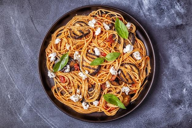Паста алла норма - традиционная итальянская еда с баклажанами, помидорами, сыром и базиликом.