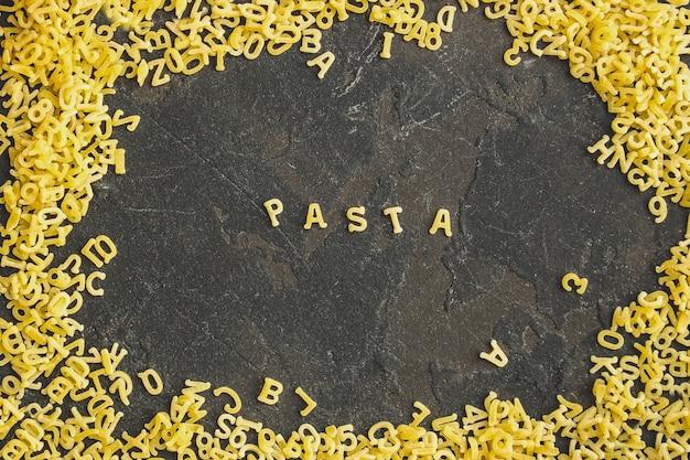 パスタアルファベットとソースの材料(材料のセット、生パスタ)2番目のコースを提供しています。トップ食品の背景。コピースペース