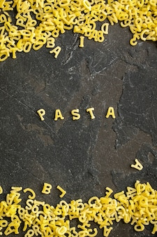 Pasta alphabet and ingredient for sauce (set of ingredients, raw pasta) serving second course. top food background. copy space