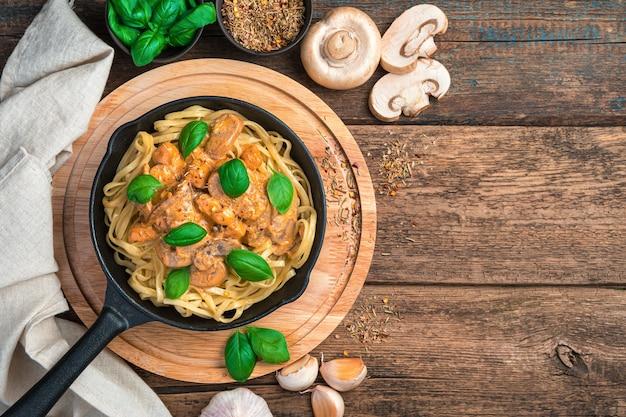 Паста и курица и грибной соус с базиликом и чесноком на деревянном столе. скопируйте пространство.