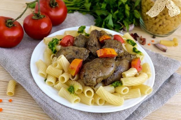 파스타와 흰색 표면에 페스토와 토마토와 함께 튀긴 거위 간 (닭, 오리).