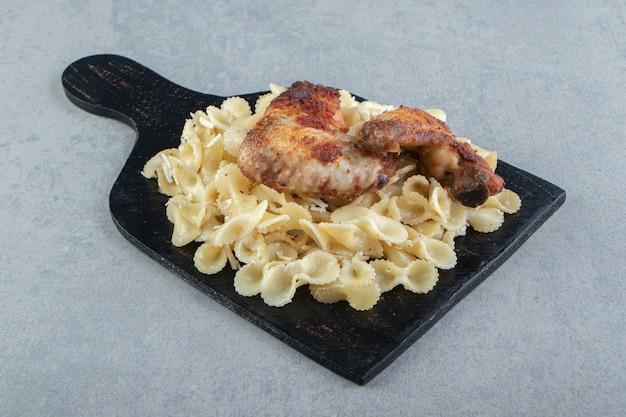 Паста и курица-гриль на черной доске.