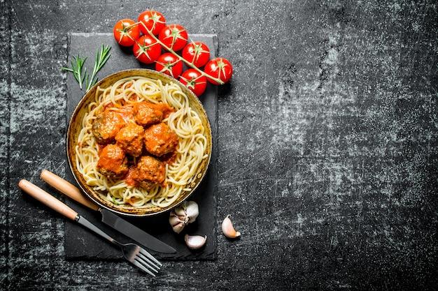 にんにくとトマトの古い鍋にパスタとミートボール。黒の素朴な背景に