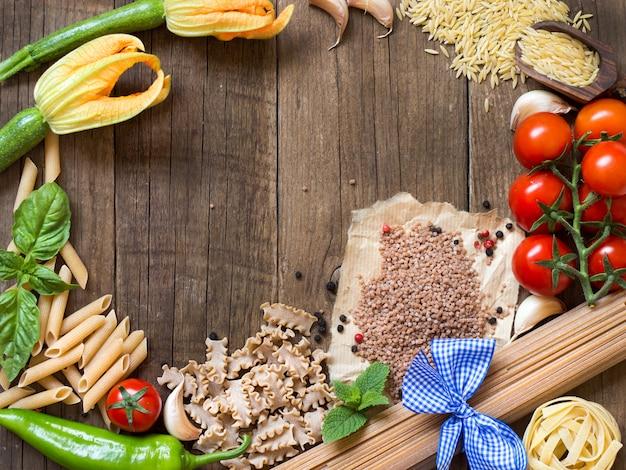 Паста и сырые овощи на деревянном фоне вид сверху с копией пространства