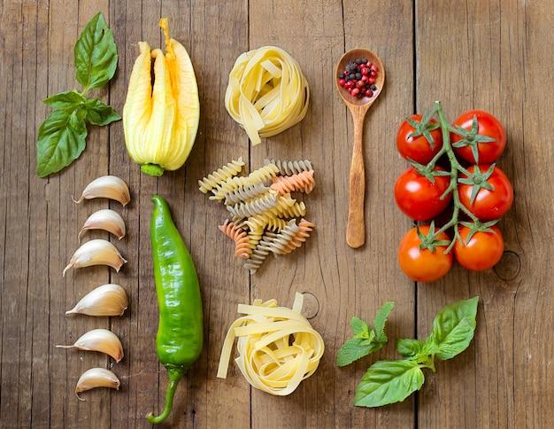 コピースペースを持つ木製の背景上面にパスタと生野菜