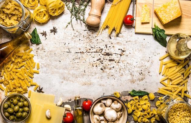 Фон макаронных изделий. сухая паста с овощами, грибами, сыром и зеленью. на деревенском фоне. свободное место для текста. вид сверху