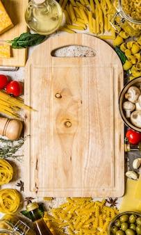 Фон макаронных изделий. сухая паста с овощами, грибами, сыром и зеленью на пустой тарелке. на деревенском фоне. свободное место для текста. вид сверху