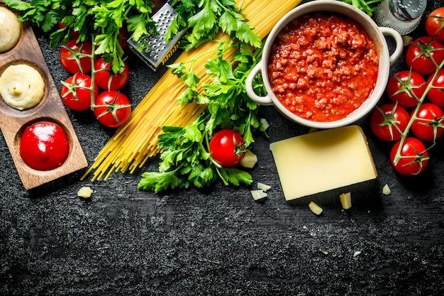 파스타 배경. 볼로냐 소스, 허브, 토마토, 치즈를 곁들인 드라이 스파게티. 검은 소박한 배경에