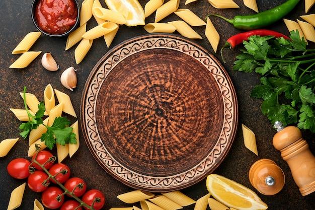 パスタの背景。パスタリガティ、トマトケチャップソース、オリーブオイル、スパイス、パセリ、フレッシュトマトをダークスレートのテーブルに。料理の背景。コピースペースのある上面図。