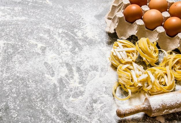 パスタの背景。卵と麺棒のパスタ。石のテーブルの上。テキスト用の空き容量。上面図