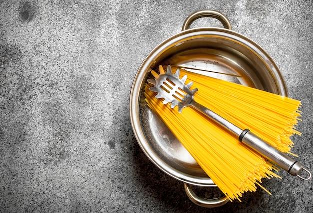 Фон пасты спагетти в горшочке с половником на деревенском фоне