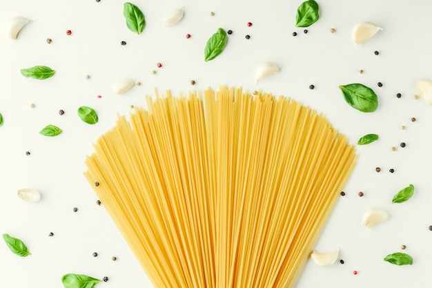 Pasta, basil, garlic and pepper on a white background