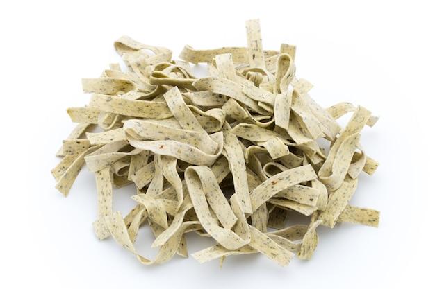 白い表面に分離されたパスタバジル。パスタは伝統的なイタリア料理の主食です