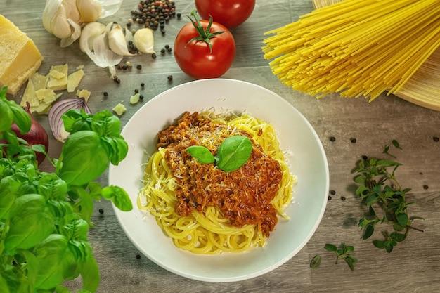 Pasta alla bolognese con ingredienti su un tavolo di legno