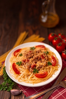 Pasta bolognese with tomato sauce and minced meat, grated parmesan cheese and fresh parsley - homemade healthy italian pasta