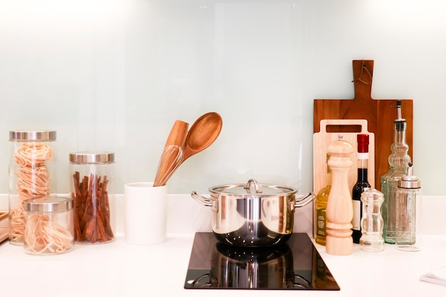 Pasta bottles, cinnamon bottle, olive oil botlte, balsamic vinegar bottle and some kitchenware put on the counter