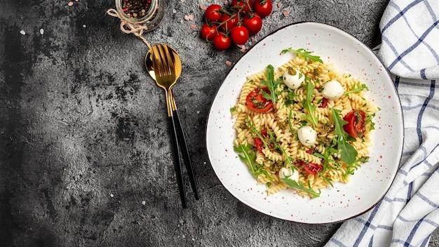 Паста салат капрезе с помидорами, моцареллой. формат длинного баннера, вид сверху.