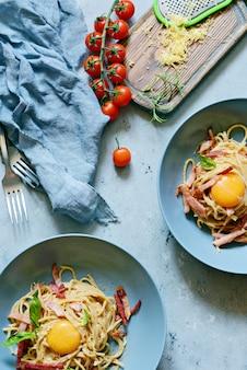 テーブルの上の灰色の皿にベーコンとパルメザンチーズのパスタカルボナーラ、青い壁にレストランのレストラン。伝統的なイタリア料理。家庭の夕食。上からの眺め