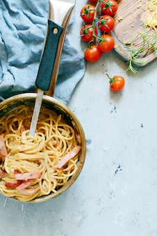 Паста карбонара с беконом и пармезаном в серых тарелках на столе, ресторан подаются на синей стене. традиционная итальянская кухня. домашний семейный ужин. вид сверху