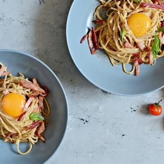 테이블에 회색 접시에 베이컨과 파마산 파스타 까르보나라, 레스토랑 제공