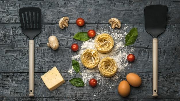 Паста, сыр, грибы и помидоры кухонными лопатками на деревянной поверхности. ингредиенты для приготовления макаронных изделий.