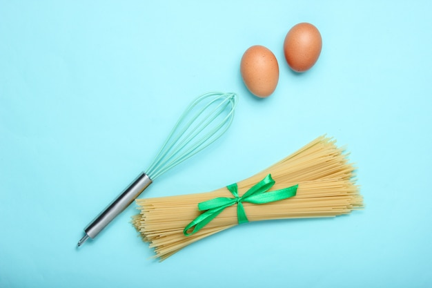 Pasta, chicken eggs and whisk on blue. top view, flat lay style