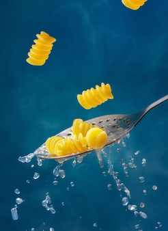 Pasta and colander on a blue background