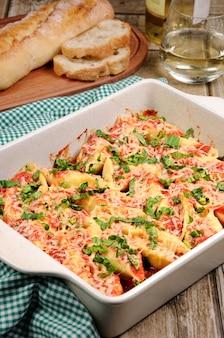 パスタコンキリエの殻にほうれん草とトマトソースを詰めた肉のミンチパルメザンチーズ