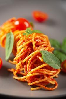 Паста, приготовленная в ресторане в томатном соусе с помидорами черри и базиликом, подается на серой тарелке.