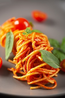 Pasta cooked in a restaurant in tomato sauce with cherry tomatoes and basil and served on a gray plate