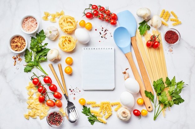 Pasta cooking background with notepad for text, tomatoes, herbs, mushrooms, eggs scattered on light marble background, top view. italian cuisine concept