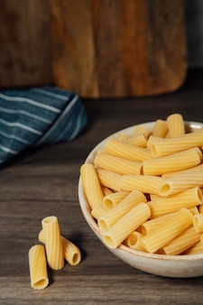 Pasta dish with a handful of raw rigatoni