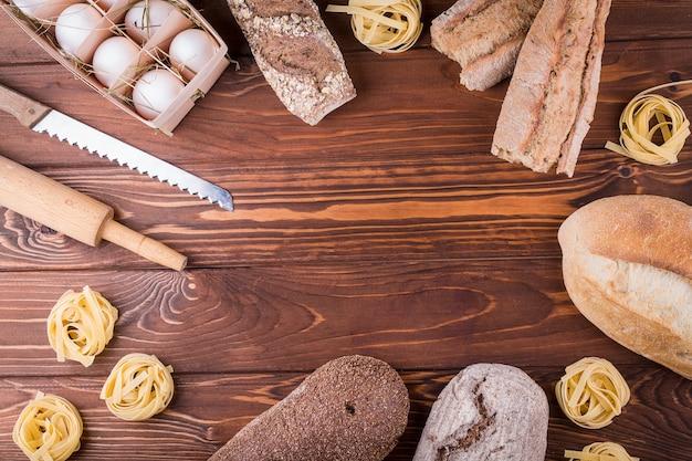 Макаронные изделия, яйца и хлеб на деревянных фоне. вид сверху с копией пространства. ингредиенты для хлебобулочных изделий