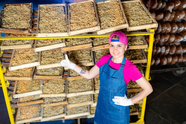 Pasta factory. production of pasta. krafted macaroni. worker with wooden boxes with pasta background.