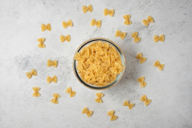 Pasta farfalle in glass bowl on white background.
