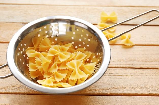 Фарфалле макароны в сушилке на деревянном столе