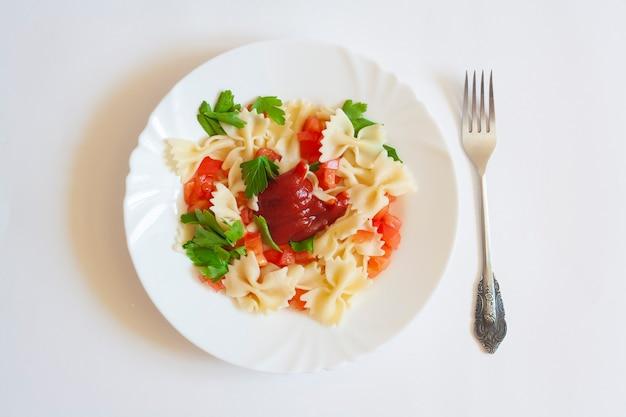 Паста фарфалле с помидорами, зеленью и соусом в тарелке и вилке, изолированные на белом фоне