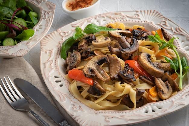 Паста fettuccine bolognese с грибами и овощами на белой тарелке. концепция меню.
