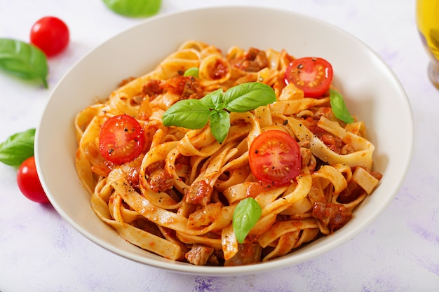 Pasta fettuccine bolognese with tomato sauce in white bowl.
